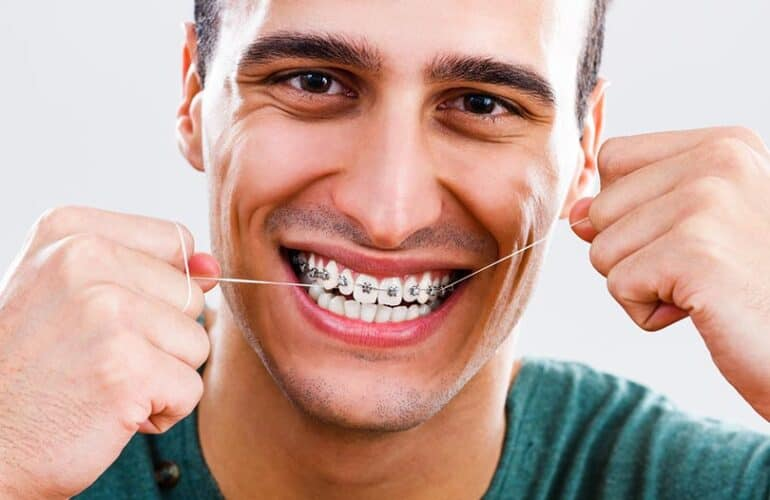 The young man is flossing his braces with smiling