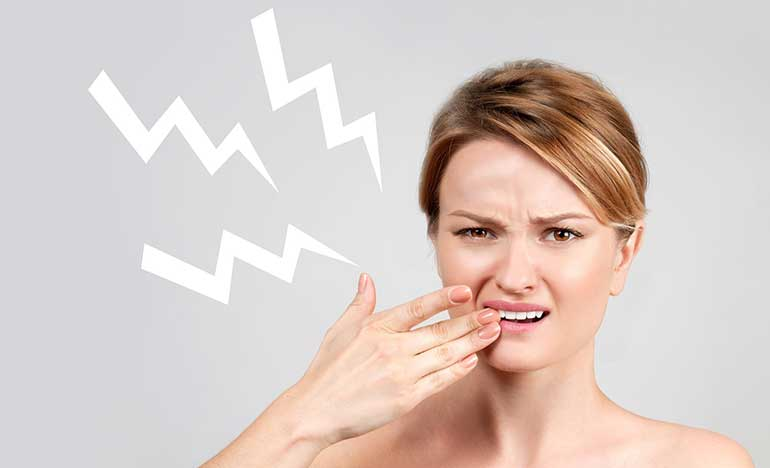Woman touching her sensitive tooth