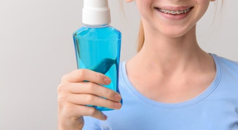 A girl with braces holding a mouthwash