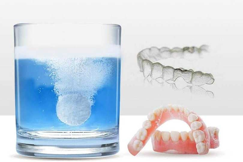 A denture, invisalign retainer and a glass of water and cleaning tablet