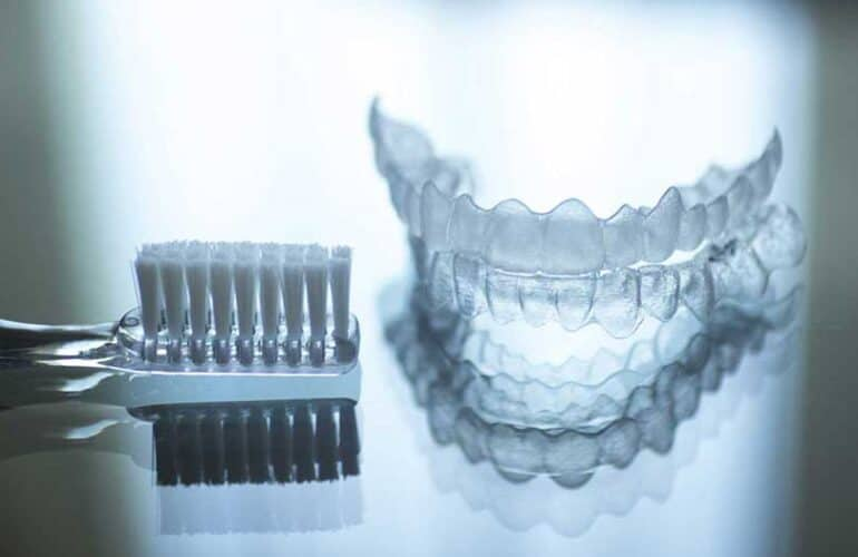 A cleaned invisalign retainer beside toothbrush