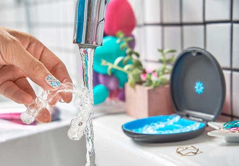 Woman washing invisalign braces under the water tap